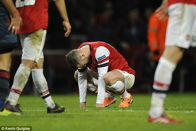On his knees: Wilshere cut a dejected figure at full time after Arsenal's morale-sapping defeat