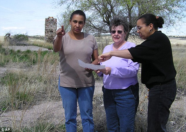 Family: In this April 26, 2004 file photo Cheryl Robinson, center, and her two daughters, Desiree Marks, left, and Tamara Kamara read a map outlining various landmarks at Wounded Knee, South Dakota. FBI documents released this week confirm Ray Robinson, Cheryl's husband and Desiree and Tamara'a father, was killed at the site during a 71-standoff between the American Indian Movement and federal agents in 1973