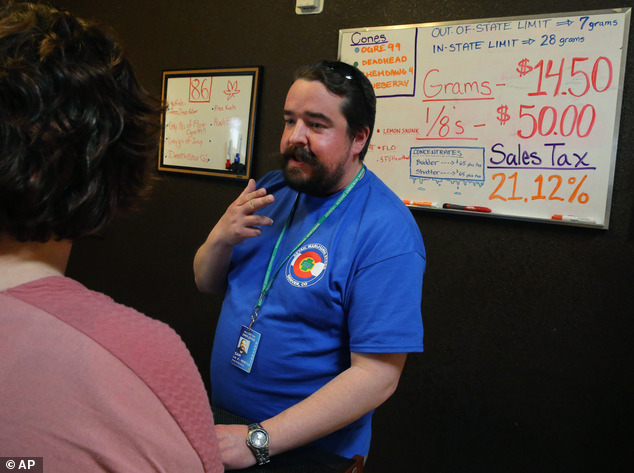 Pot store employee Sam Walsh informs a first time customer about different strains of marijuana, a white board listing prices and sales tax, inside the retail shop at 3D Cannabis Center, in Denver on February 14