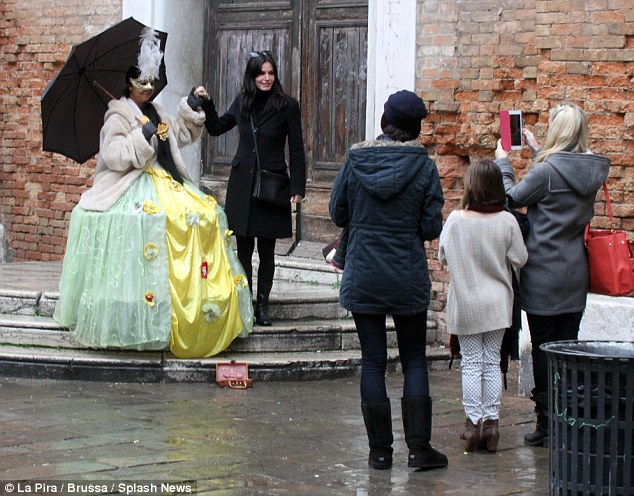 Strike a pose: The star held a street performer's hand as they walked along the street and stopped to watch the show