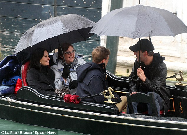 Brollies up: The star sat underneath an umbrella as she was taken up and down the Venetian canals