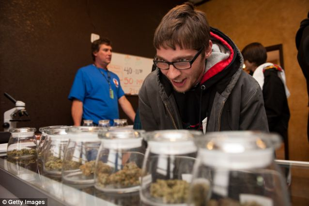 Tyler Williams of Blanchester, Ohio, selects marijuana strains to purchase at the 3-D Denver Discrete Dispensary back on January 1, when the drug was first legalized