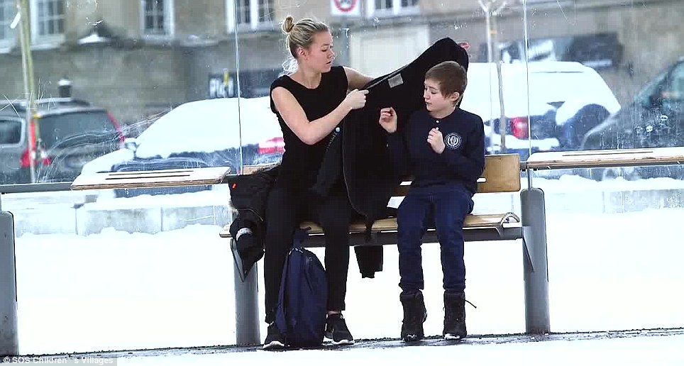 Warm heart: She takes off her own jacket and wraps it around the freezing boy