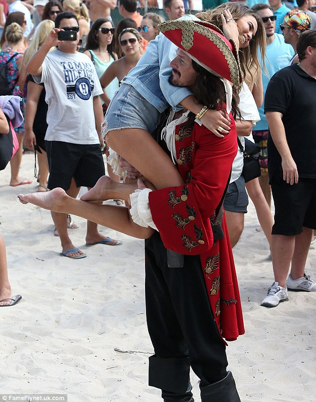 Holding up the rear: Chrissy flashed her derriere in ripped shorts as Captain Morgan carried her over his shoulder at Sports Illustrated's Volleyball Tournament sponsored by the rum brand in Miami beach earlier on Thursday