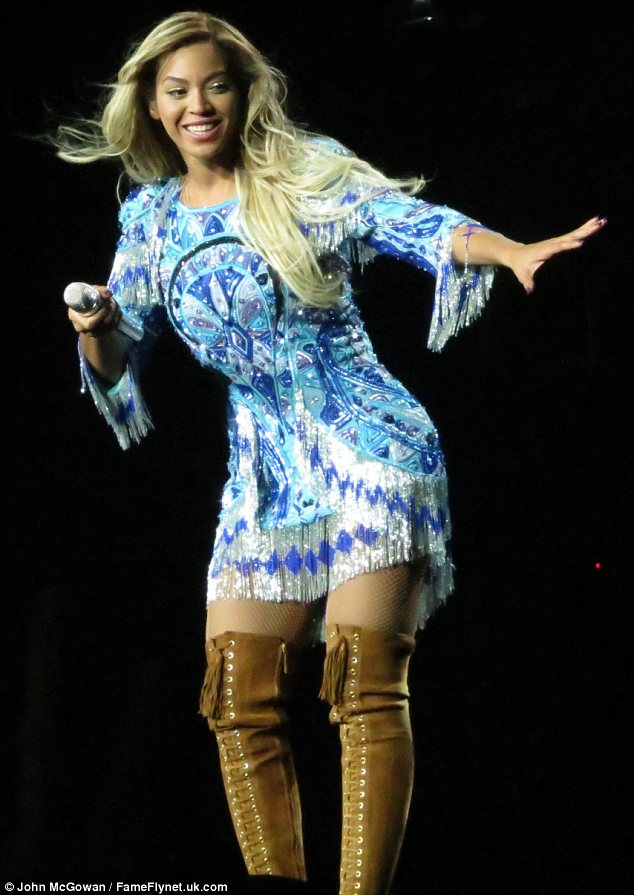 Mixing it up: The singer went for a Seventies style look in this frayed dress and suede knee high boots