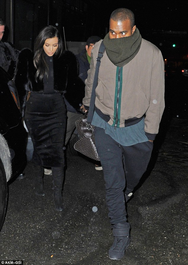 Casual for a change: Kanye meanwhile was far less dressed up, wearing a pair of loose fitting but tapered black pants with a teal T-shirt and a bomber jacket for warmth