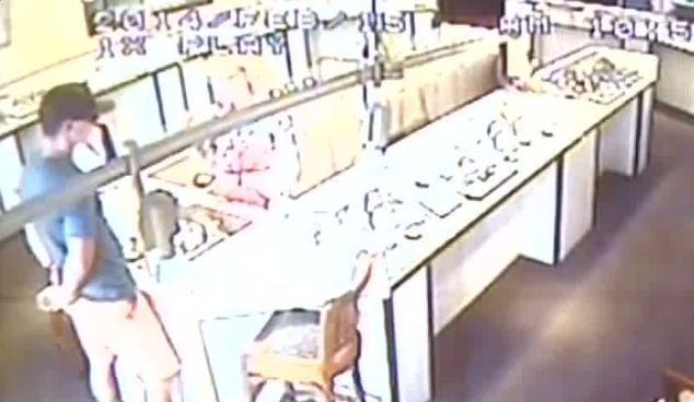 This is the scene in a Cairns diamond jeweller seconds before the man in the baseball cap, identified as 29-year-old Briton Matthew Osborne allegedly stole a rare pink diamond worth £135,000