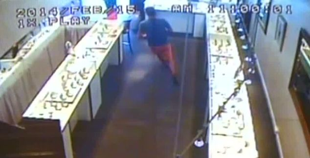 The man runs to the door of a diamond shop in Cairns, Queensland. He reportedly then fled on bicycle
