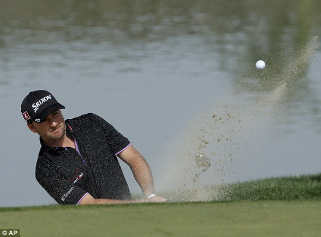 Out of a hole (again): Graeme McDowell hits out of a bunker during his match against Hunter Mahan