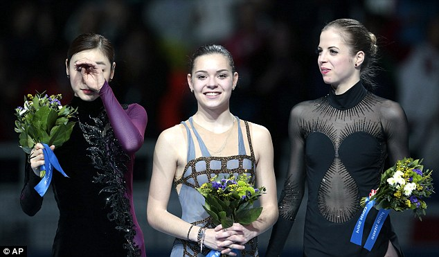 Controversial win: Adelina Sotnikova of Russia (center), Yuna Kim of South Korea (left) and Carolina Kostner of Italy stand on the podium during the flower ceremony for the women's free skate figure skating final at the Iceberg Skating Palace