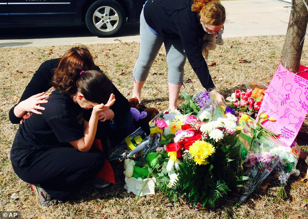 Too much: Stacey Barfield, mother of Hailey Owens, foreground left, is consoled by Sara Wells, as family member Teri Nord, right, arranges flowers left by well wishers near the site where the 10-year-old girl was abducted