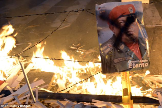 A poster of Venezuelan late President Hugo Chavez remains near a burning barricade during an anti-government demo in Caracas