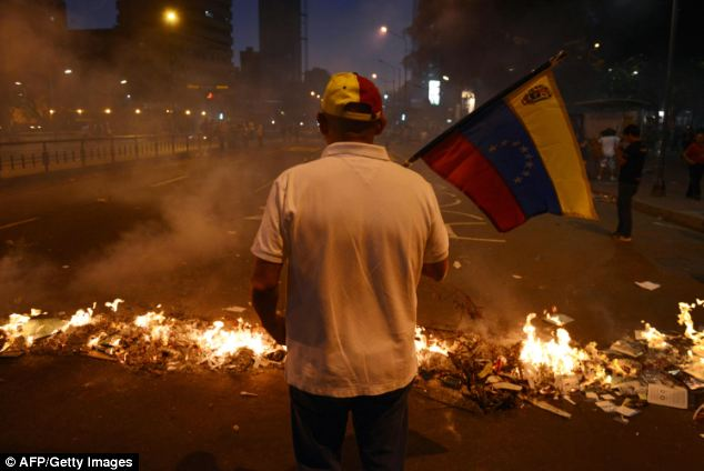 A man holds a Venezuelan national flag next to a barricade during an anti-government demo in Caracas