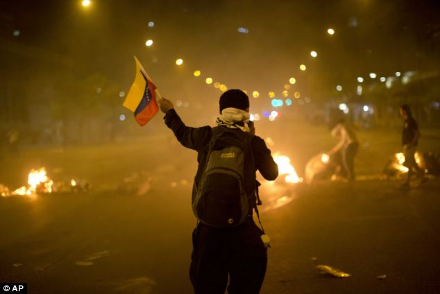An anti-government demonstrator waves Venezuela's national flag in front of a burning barricade in the Altamira neighborhood of Caracas