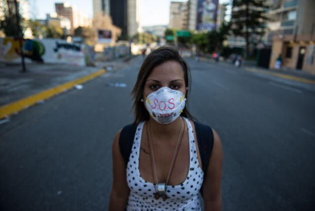 A student between the barricades with a message written on her mask that reads 'SOS Venezuela'