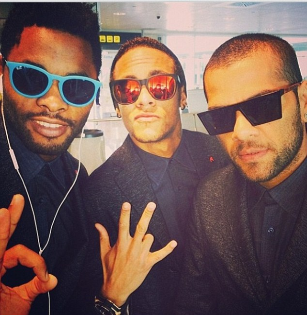 Alves (right) looked dapper with teammates Alex Song (left) and Neymar