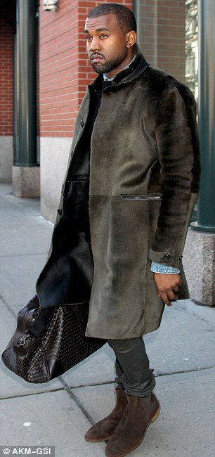 Chic and sleek: The hip hop artist wore a knee-length fur coat with black leather trousers and brown suede shoes while toting a Bottega Veneta bag