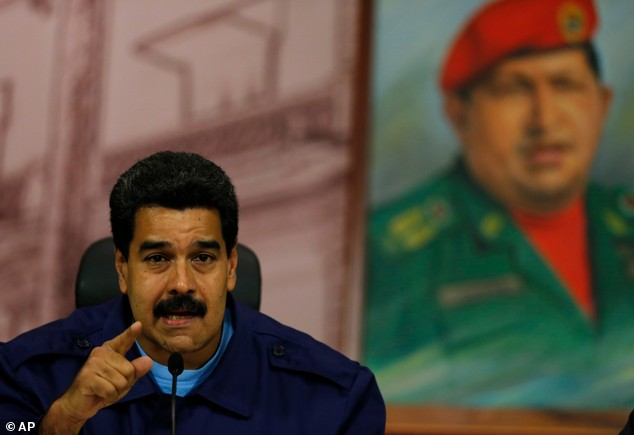 Venezuela's President Nicolas Maduro speaks next to a painting of the late Hugo Chavez, during a news conference at Miraflores Presidential Palace in Caracas yesterday