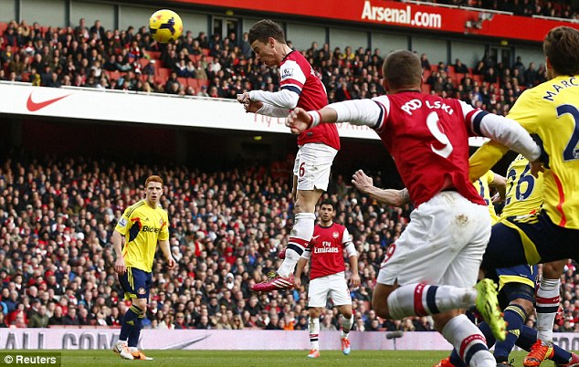 Leap of faith: Laurent Koscielny rises highest to head home Arsenal's fourth goal in the second half