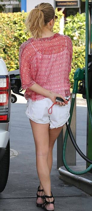 Stylish: LeAnn teamed the shorts with a white vest top and red jumper
