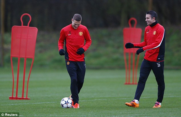 On the ball: Manchester United defender Nemanja Vidic (left) trains with Robin van Persie on Monday