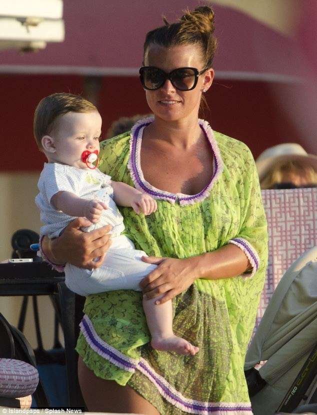 Family: The WAG looked gorgeous in a lime green kaftan as she cuddled her nine-month-old son Klay