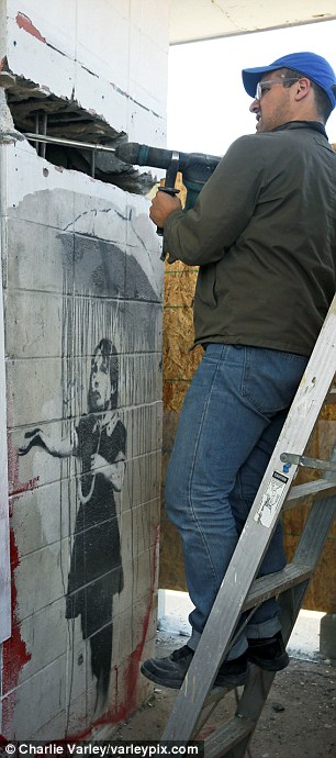 Chipping away: A man who identified himself only as Chris takes a heavy duty drill to the Banksy art work 'Girl with Umbrella'