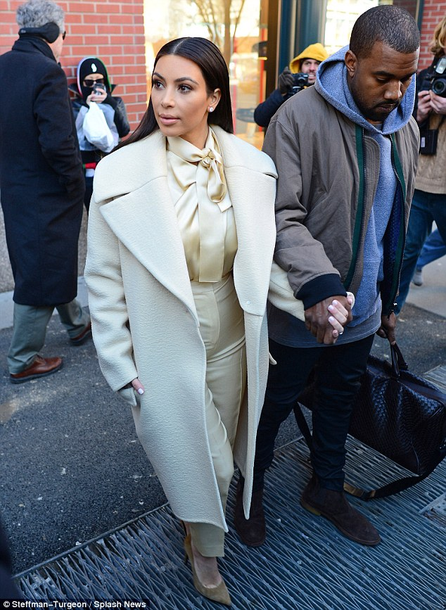 Keeping a straight face: Kim appeared emotionless as she stepped out in the cold holding hands with Kanye on Monday