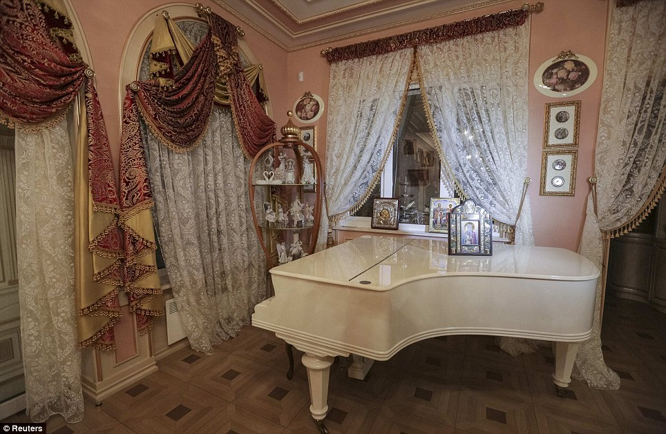 Ornate drapes hang behind a white grand piano. The walls, ceiling and floors are a decorated with intricate detailing