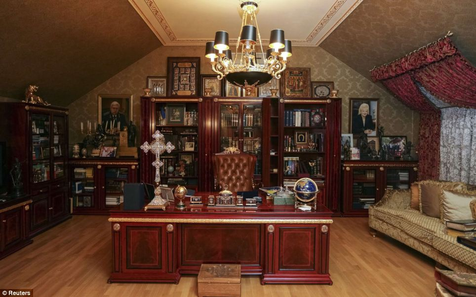 Decadent: The opulence of Pshonka's house can be seen in everywhere.  His portrait, in uniform, is on the left, while the woman on the right is believed to be his wife. The cross on his desk and icons on the top of the bookscase reflect his Orthodox faith