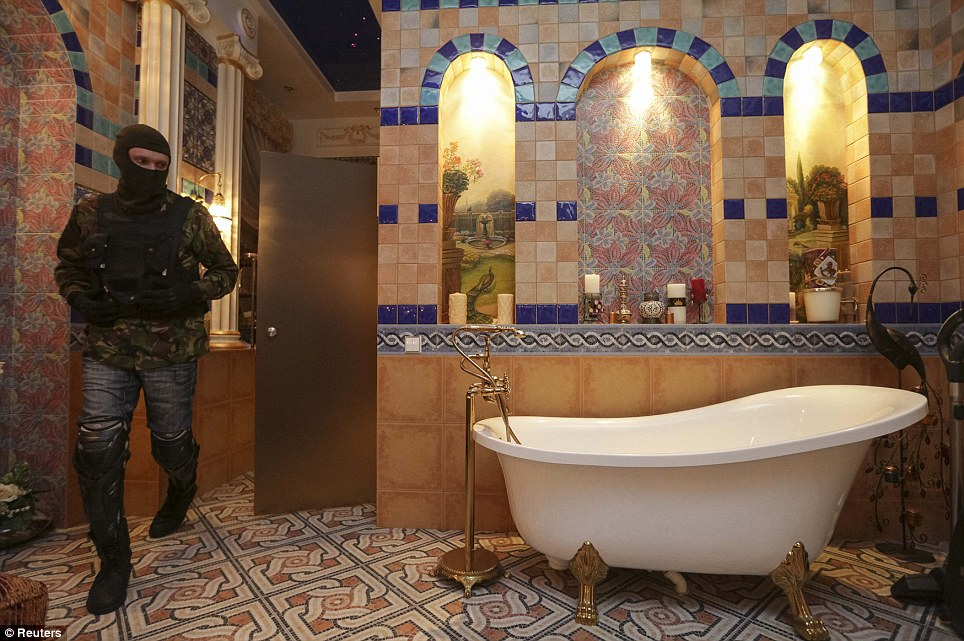 A man wearing a balaclava walks through a bathroom decorated with ornate tile work on the floor and walls and a luxury bath tub