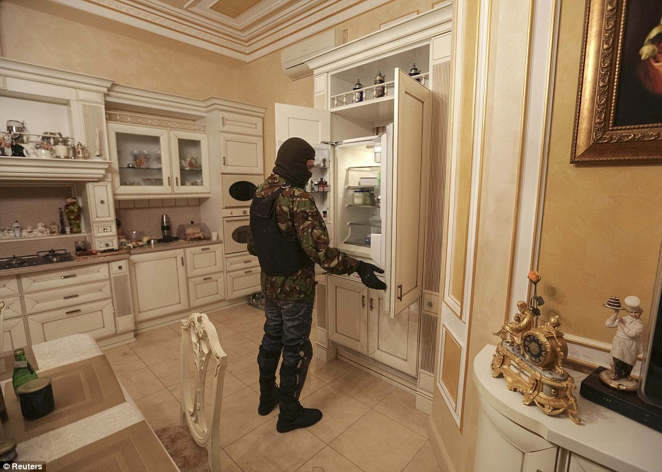 A man inspects the contents of a fridge, which still has items in it. Even the kitchen oozes decadence with detailed paneling throughout and ornamental pieces