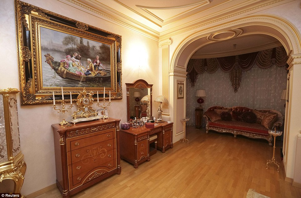 A decorative arch opens to a plush lounge and lamp, which is the centrepiece of this lavish room with wooden floors