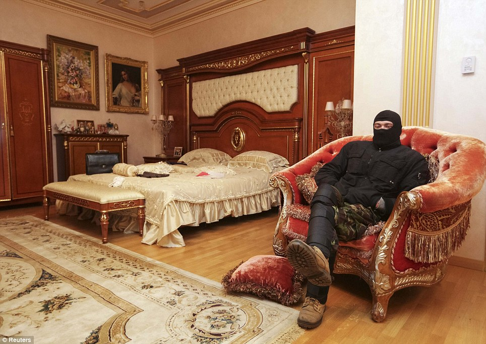A man takes some time out to sit on an ornate chair in a grand bedroom featuring a superior wooden bedhead and giant rug