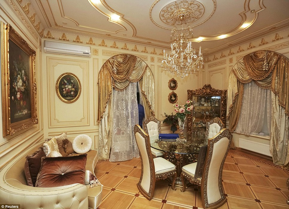 A decadent sitting room with deluxe drapes, ornate chairs and table and giant chandelier. The walls and ceiling have also been decorated with intricate patterns