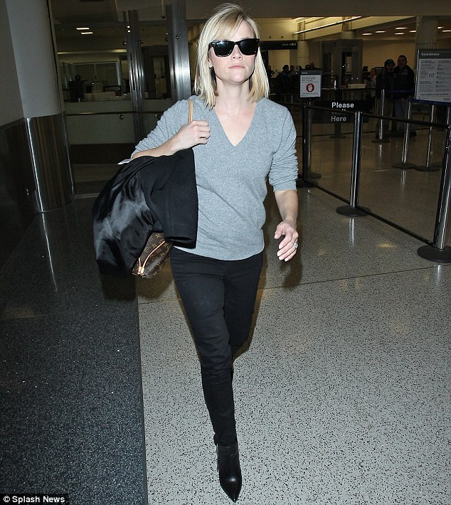 She's off again: Reese was later seen catching a flight out of LAX airport
