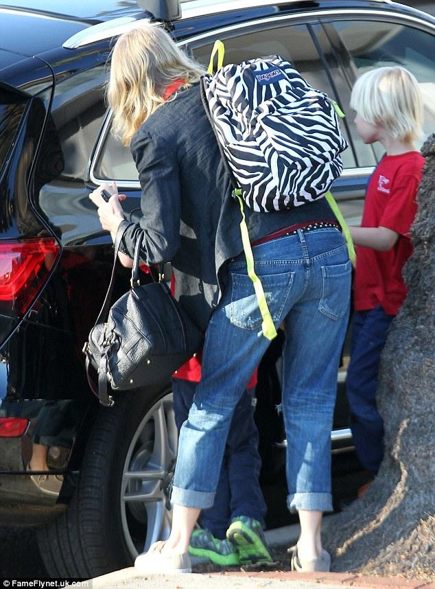 Designer rucksack? Naomi works her youngest son's zebra print rucksack as she bundles them into her car