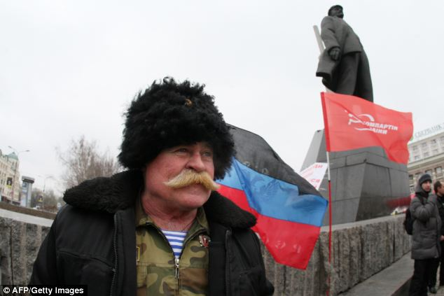 An activist of the Ukrainian Communist party together with a few others stands at the Lenin monument in the centre of the industrial city of Donetsk, reportedly to prevent it destruction by Maidan supporters