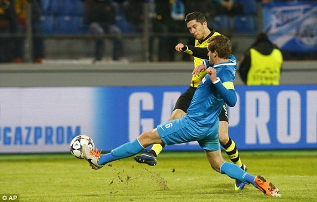 On target: Two-goal hero Lewandowski shoots at goal past Zenit defender Nicholas Lombaerts