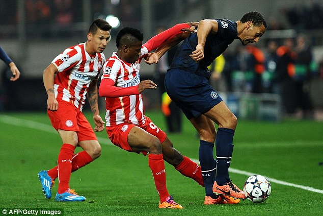 Under pressure: Rio Ferdinand (right), pictured here being challenged Olaitan, endured a disappointing night in United's defence