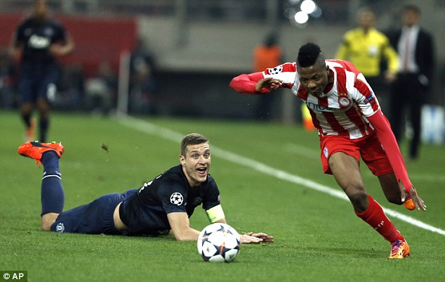 Down and out: Captain Nemanja Vidic (left), who will leave Old Trafford this summer, watches as Olympiacos' Michael Olaitan (right) gets away from him