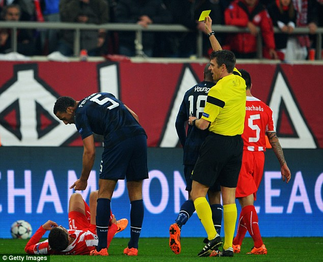 Booked: Ferdinand receives a yellow card from referee Gianluca Rocchi after a mistimed challenge