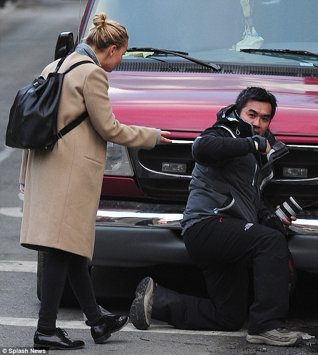 Backed into a corner: Li was seen kneeling on the ground and back into a bonnet of a car