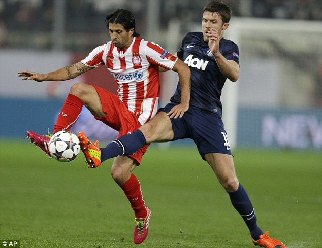 In vain: Carrick struggles for the ball in midfield with Olympiacos' Alejandro Dominguez