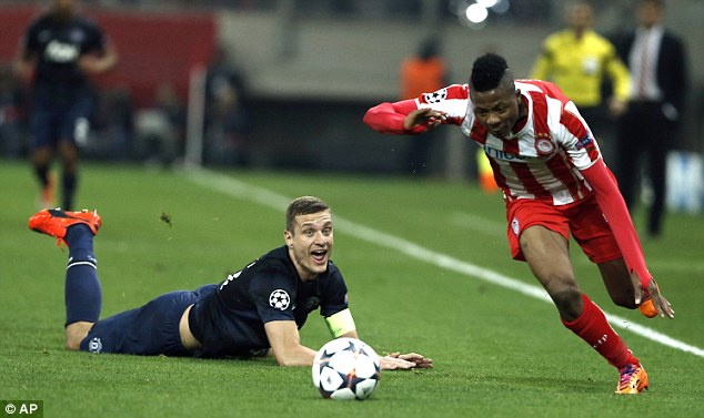 In his wake: Olympicos star Michael Olaitan races past United defender Nemanja Vidic, left on the floor