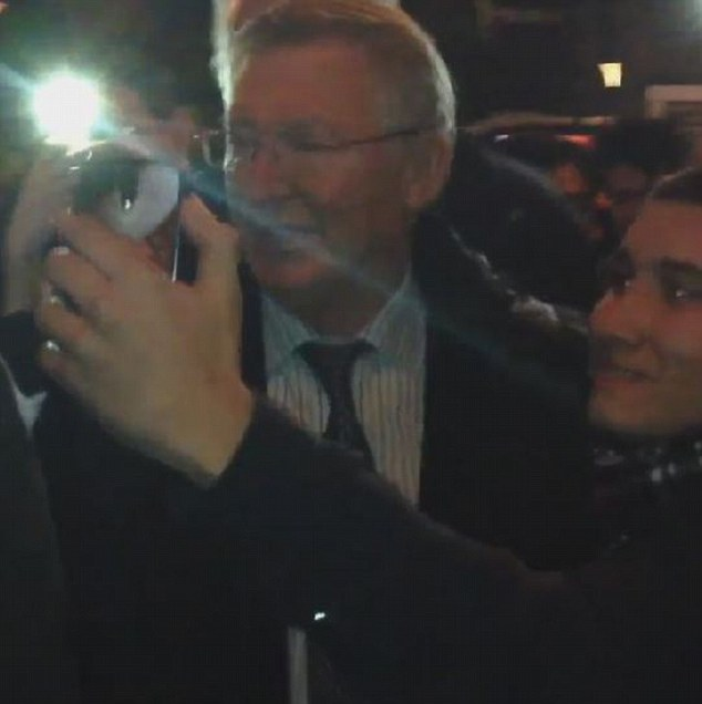 Say cheese: Former Manchester United boss Ferguson (left) gets his picture taken with another fan