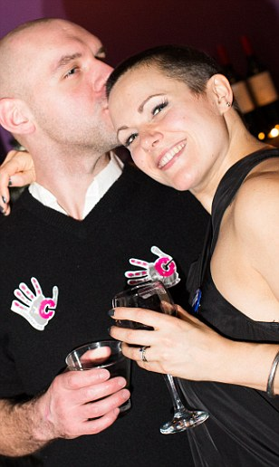 Lizzie and her husband share an embrace after her hair have been shaved