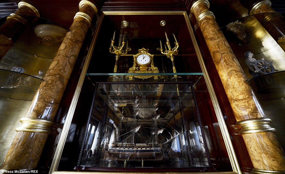 A pair of candelabras, a gilded closk and a model of a ship in a glass cage