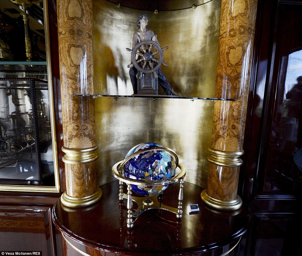 An elaborate globe and a statuette of a ship's helmsman sit between two columns