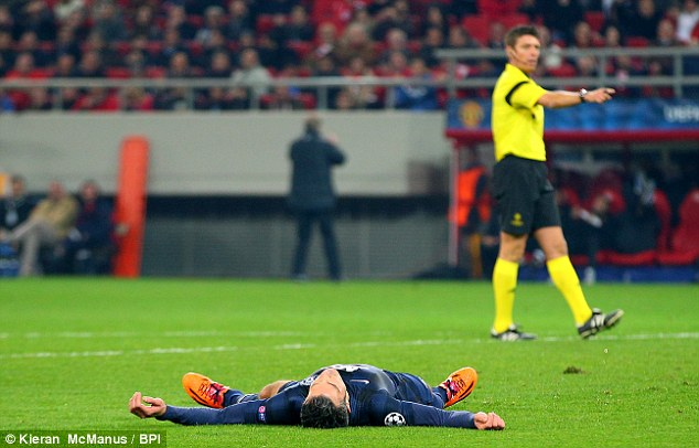 Stuck: Manchester United frontman Robin van Persie lies in despair after the 2-0 defeat to Olympiacos